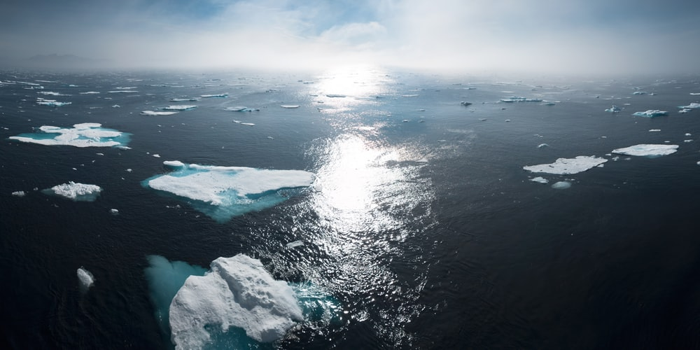 photo of ice bergs floating in the ocean. The sky is blue in the background and cloudy, and the sun is reflected in the middle of the image.
