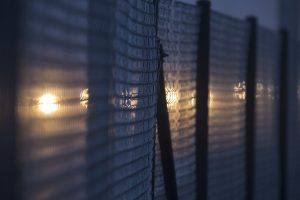 image of a wire fence at night, backlit by orange lights